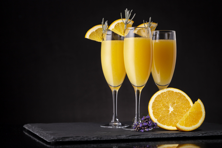 Mimosa cocktails in champagne glasses with orange juice and sparkling wine decorated with lavender leaves and orange slices Stockfoto