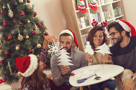 Young frineds having fun while making paper snowflakes and Christmas decorations