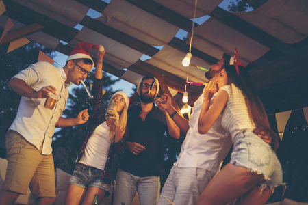 Group of young friends dancing, blowing party whistles, drinking and having fun at an outdoor New Years Eve party. Focus on the guy in the middle