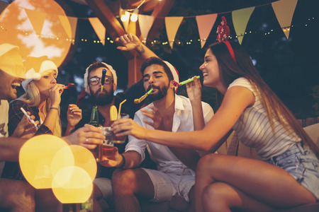 Group of young friends blowing party whistles, drinking beer and having fun at an outdoor New Years Eve party. Focus on the guy on the right Stock Photo