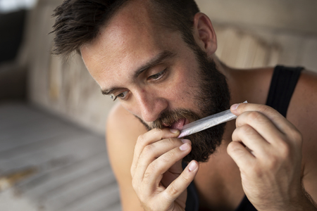 Young man rolling a joint, licking the rolling paper in order to seal it Stock Photo