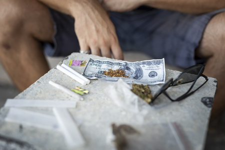 Detail of male hands rolling a joint. Focus on the tobacco on the banknote Stock Photo