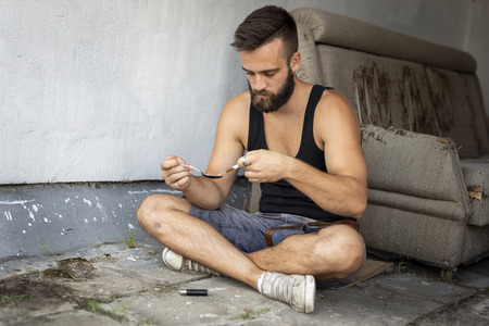 Intravenous junkie filling up a heroin syringe getting cooked heroin from a spoon, getting his shoot up dose ready Stock Photo
