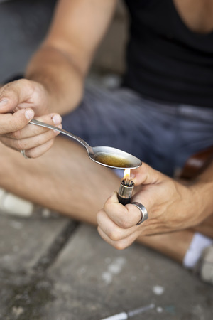 Detail of male hands cooking heroin in a spoon with a lighter, gettingit ready for intravenous use. Selective focus on the spoon Stock Photo