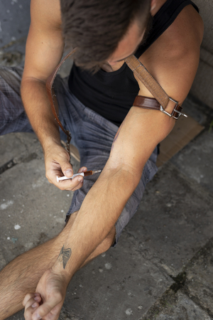High angle view of an intravenous drug user applying heroin injection into a vein. Focus on the needle Stock Photo