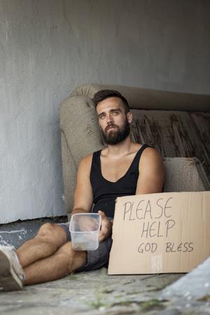 Homeless man sitting in the street, begging for money