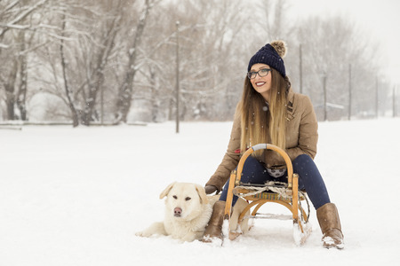 Young girl sitting on a sleigh cuddling her dog while dog is lying in the snow next to the sleigh, both enjoying a winter day in nature