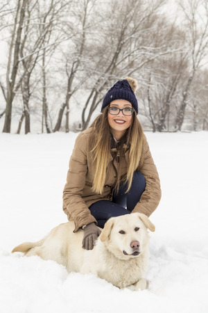 Beautiful young woman cuddling her dog and enjoying a snowy winter day in nature
