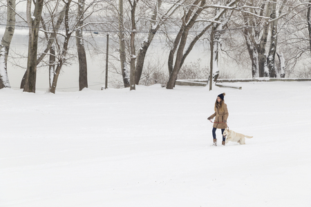 Young beautiful woman walking in the snow with her dog on a snowy winter day