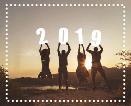 Silhouette of a group of friends jumping near a seaside cliff, holding numbers 2019 and looking at a beautiful sunset at Valtos beach in Parga, Greece
