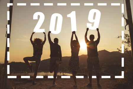 Silhouette of a group of friends standing near a seaside cliff, holding numbers 2019 and looking at a beautiful sunset at Valtos beach in Parga, Greece Stock Photo