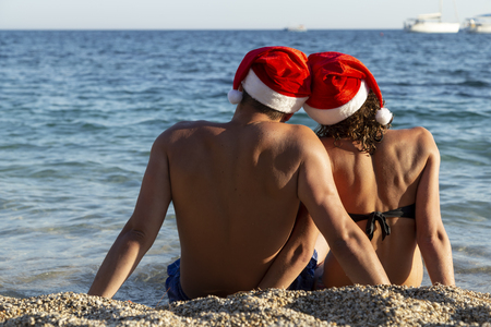 Couple in love wearing Santa hats, sitting on the beach, looking towards the horizon and enjoying holidays and vacation at seaside