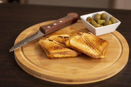 Detail of hot sandwiches on a wooden cutting board ready for eating. Selective focus on the sandwiches Stock Photo
