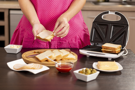 Detail of female hands adding salami on a sandwich; woman making hot sandwiches for breakfast in a sandwich maker. Selective focus on the hands and the sandwich