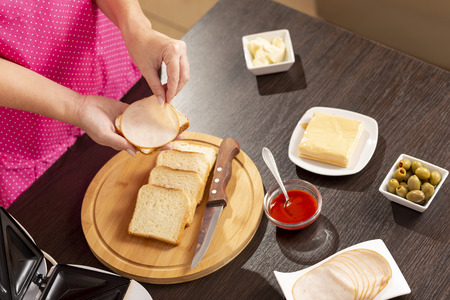 Detail of female hands adding salami on a sandwich; woman making hot sandwiches for breakfast in a sandwich maker. Focus on the hands and the sandwich Stock Photo
