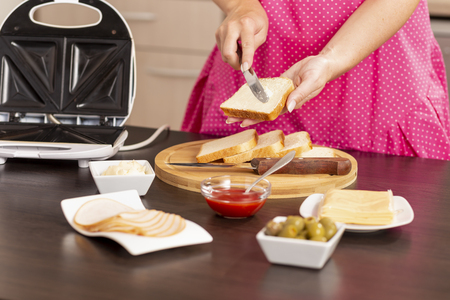 Detail of female hands spreading butter over a bread slice; woman making hot sandwiches in a sandwich maker for breakfast. Focus on the knife