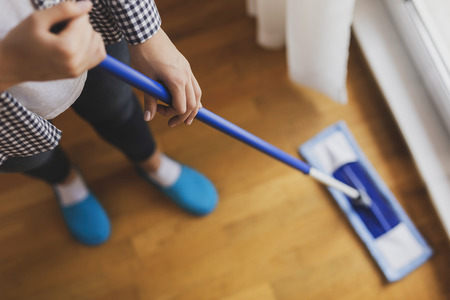High angle view of woman holding a floor wiper and wiping floor, keeping the daily home hygiene. Focus on the hand holding the floor wiper