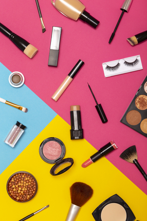Flat lay of various make up products on colorful background. Make up brushes, blushes, face powders, corrector, highlighters, lip gloss, lipstick, mascara, eyeliner and eyelashes Imagens