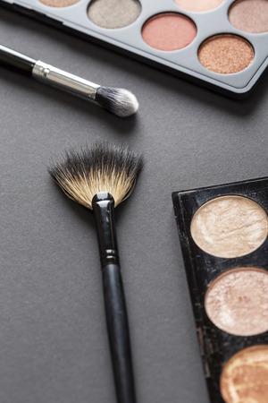 Hohe Betrachtungswinkel einer Lidschatten-Palette, Highlighter-Palette, Highlighter-Make-up-Pinsel und eines Augenlid-Make-up-Pinsels