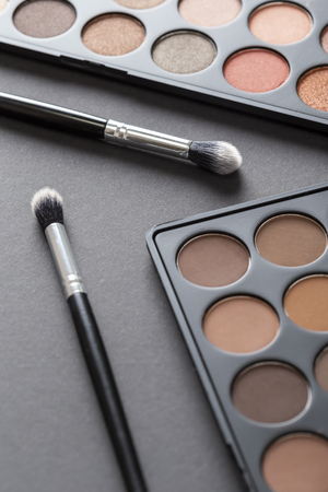 High angle view of eyeshadow palettes and eyelid make up brushes