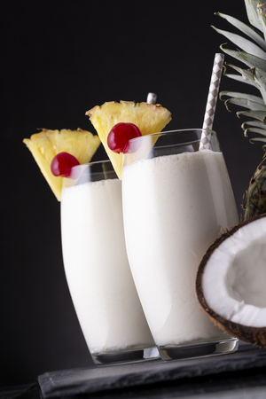 Two glasses of pina colada cocktail with dark rum, pineapple juice and coconut cream, decorated with pineapple slices and maraschino cherry