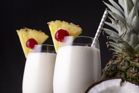 Detail of two glasses of pina colada cocktail with dark rum, pineapple juice and coconut cream, decorated with pineapple slices and maraschino cherry
