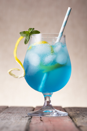Blue lagoon cocktail with blue curacao liqueur, vodka, lemon juice and soda, decorated with lemon slice and mint leaves