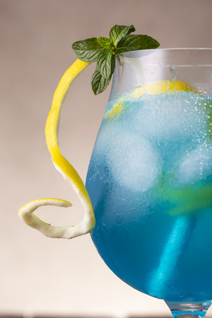 Detail of a glass of blue lagoon cocktail with blue curacao liqueur, vodka, lemon juice and soda, decorated with lemon slice and mint leaves