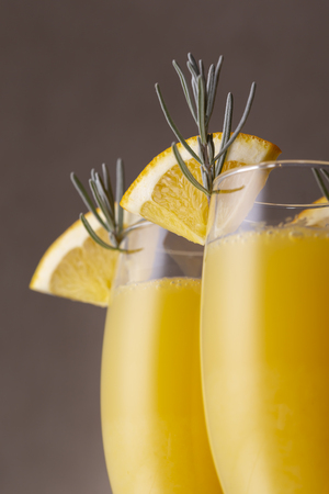 Detail of mimosa cocktails in champagne glasses with orange juice and sparkling wine decorated with lavender leaves and orange slices Zdjęcie Seryjne