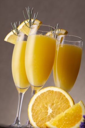 Mimosa cocktails in champagne glasses with orange juice and sparkling wine decorated with lavender leaves and orange slices Zdjęcie Seryjne