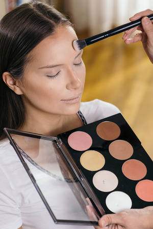 Make up artist working in a make up studio, applying the highlighters to female clients face