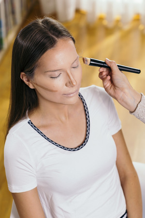 Make up artist applying liquid face powder foundation to a female clients face and blending contours