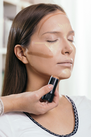 Make up artist applying face powder and corrector foundation to a female clients face, contouring the face