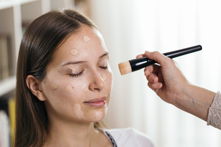 Make up artist applying liquid face powder foundation to a female clients face with a make up brush Zdjęcie Seryjne