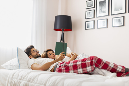 Couple in love lying in bed, hugging and reading books after waking up