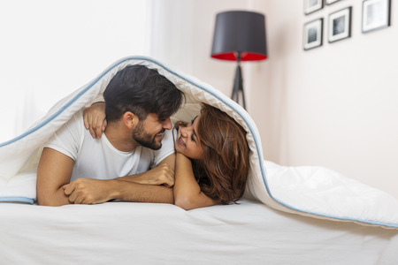 Couple in love lying under the sheets, hugging and cuddling Zdjęcie Seryjne