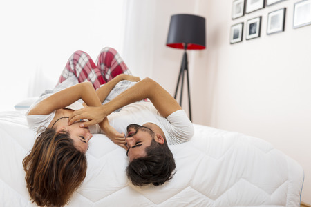 Couple having fun lying in bed and hanging upside down in the morning after waking up Zdjęcie Seryjne