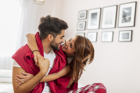 Couple in love cuddling and hugging in bed after waking up