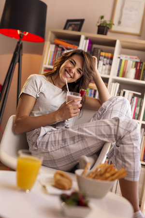 Beautiful young woman enjoying weekend morning, having breakfast and drinking a fresh strawberry smoothie Zdjęcie Seryjne