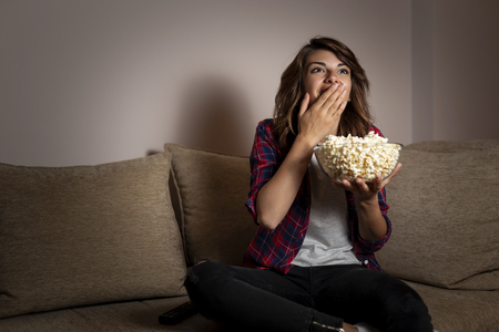 Beautiful young woman sitting in the dark on a living room couch, having fun watching TV and eating popcorn Zdjęcie Seryjne