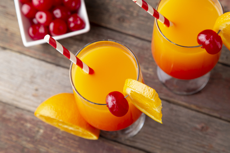 High angle view of two cold tequila sunrise cocktails with tequila, pomegranate juice and orange juice decorated with slices of orange and maraschino cherries