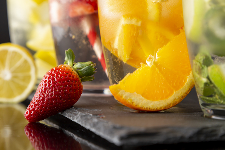 Detail of four glasses of infused water with fresh strawberries, lime, cucumber and mint leaves, lemon and orange