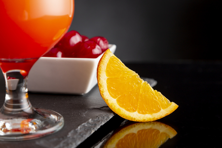 Detail of cold tequila sunrise cocktails with tequila, pomegranate juice and orange juice decorated with slices of orange and maraschino cherries