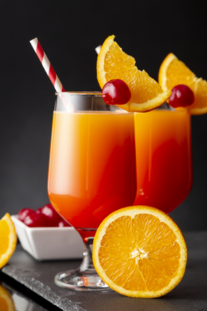 Two cold tequila sunrise cocktails with tequila, pomegranate juice and orange juice decorated with slices of orange and maraschino cherries