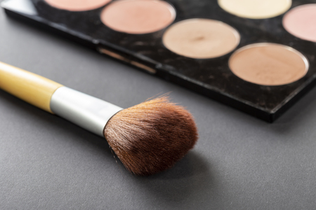High angle view of face powder palette and a make up brush isolated on black background