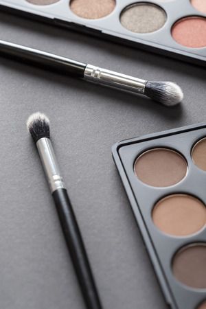 High angle view of an eyeshadow palette and an eyelid make up brush