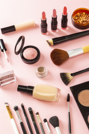 High angle view of various make up products on pink background. Make up brushes, blushes, face powders, highlighters, lip gloss, lipstick and glitters Stockfoto