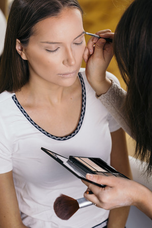 Make up artist working in a make up studio, applying the eyebrow shadows to female client's eyebrows Banque d'images