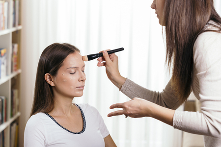 Make up artist applying liquid face powder foundation to a female client's face and blending contours