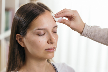 Make up artist blending liquid face powder foundation with a make up sponge to a female client's face, to get evenly blended skin tone Banque d'images